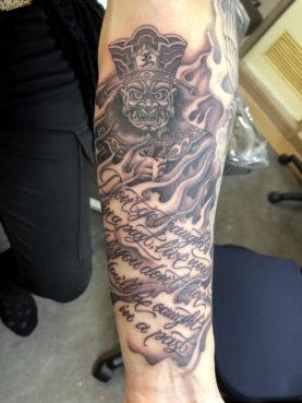 洋風に描いた閻魔大王に筆記体のスクリプトをあしらったタトゥー